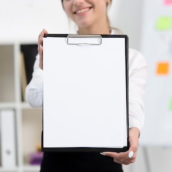 Empresaria que muestra el libro blanco en el portapapeles negro