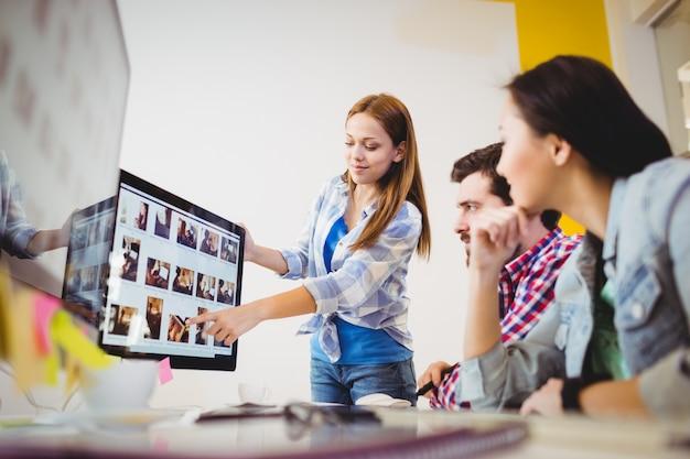 Empresaria que muestra la pantalla de la computadora a los compañeros de trabajo