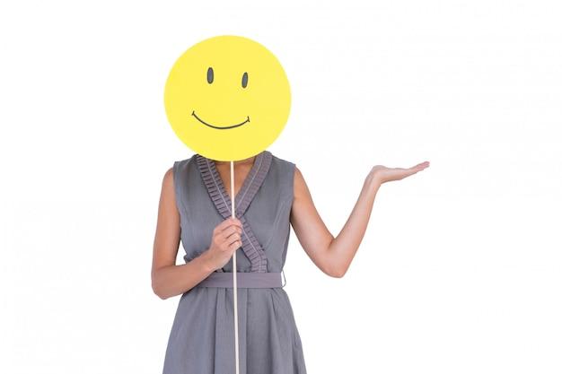 Empresaria que sostiene la cara sonriente feliz en el fondo blanco