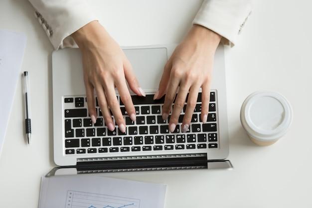 Empresaria que trabaja en la computadora portátil, manos escribiendo en el teclado, vista desde arriba