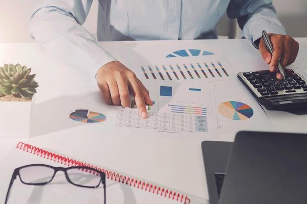 Empresaria que trabaja en el escritorio usando la calculadora que analiza la contabilidad financiera en la oficina