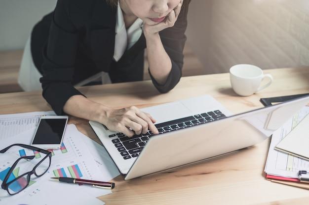 Empresaria que trabaja en la oficina de escritorio con análisis de estadísticas de marketing gráfico