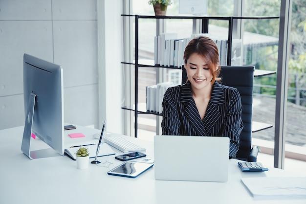 Empresaria que usa la computadora portátil mientras que trabaja en su oficina.