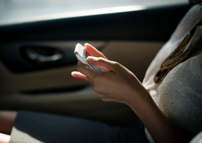 Empresaria que usa el teléfono móvil en el asiento trasero del coche