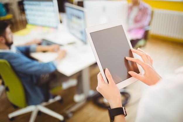 Empresaria que usa la tableta en la oficina creativa