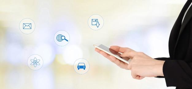 Empresaria que usa el teléfono elegante con internet del icono de las cosas en concepto borroso del fondo, del negocio y de la tecnología