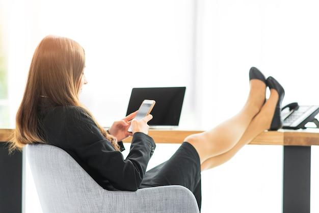 Empresaria relajante en el escritorio con teléfono inteligente en la oficina