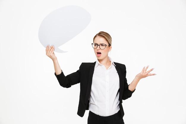 Empresaria rubia disgustada en anteojos mirando a un lado y sosteniendo el bocadillo en blanco sobre fondo blanco