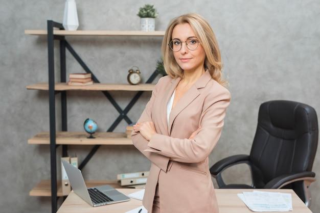 Empresaria rubia joven confiada que se coloca delante del escritorio de oficina