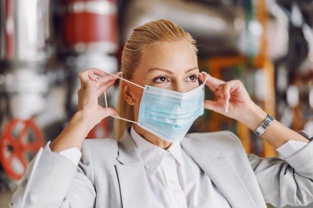Empresaria rubia en traje poniendo mascarilla mientras está de pie en su planta durante el virus corona
