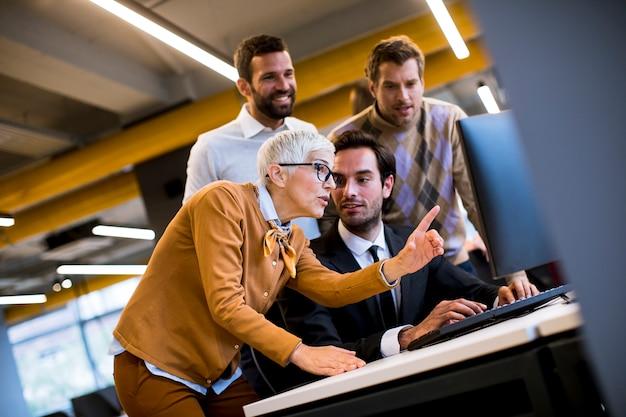 Empresaria senior y jóvenes empresarios trabajan en una oficina