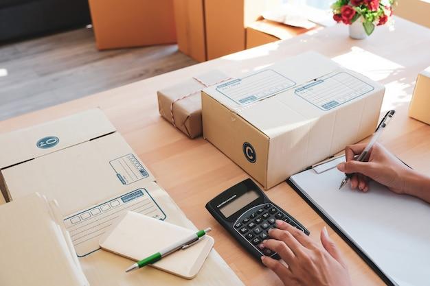 Empresaria sentada, calculando y preparando la entrega.