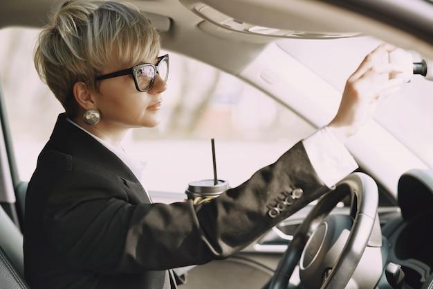 Empresaria sentada dentro de un auto y toma un café