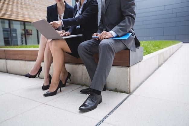 La empresaria sentada con sus colegas y usando laptop