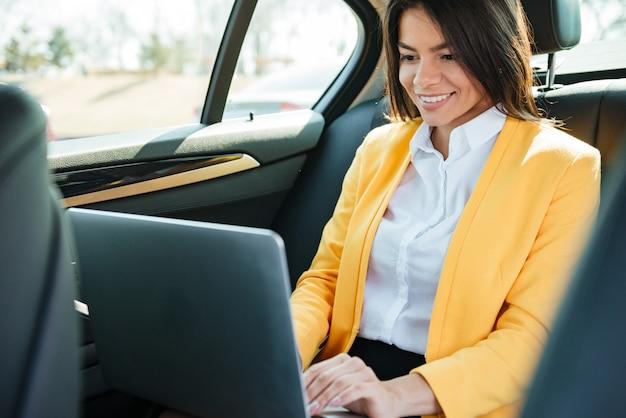 Empresaria sentado en el asiento trasero del coche y trabajando