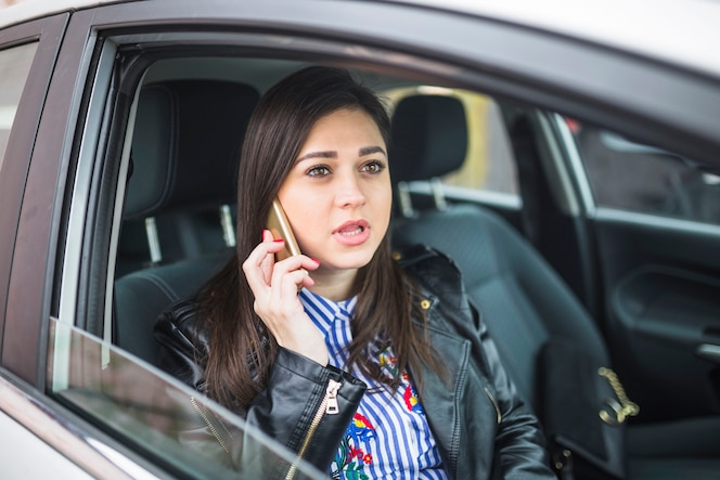 Empresaria sentado en el coche usando teléfono móvil