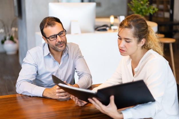 Empresaria seria mostrando papeles a ejecutivo de mediana edad