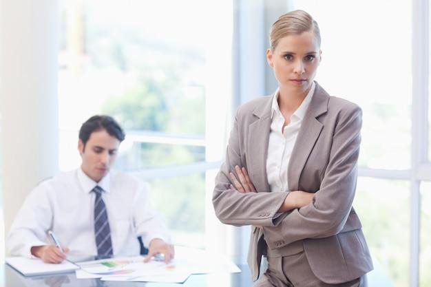 Empresaria seria posando mientras su colega está trabajando