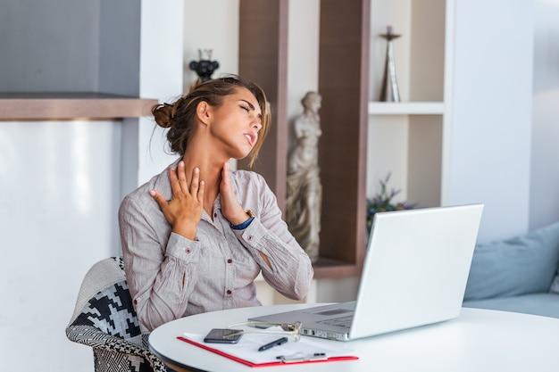 Empresaria siente dolor en el cuello después de sentarse a la mesa con el portátil.