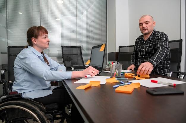 Empresaria en silla de ruedas y notas post-it naranjas