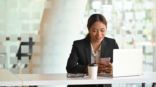 Empresaria con smartphone en el lugar de trabajo de oficina.