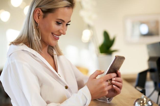 La empresaria con smartphone en la recepción del hotel