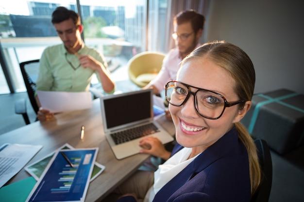 Empresaria sonriendo a la cámara mientras sus colegas leen el documento