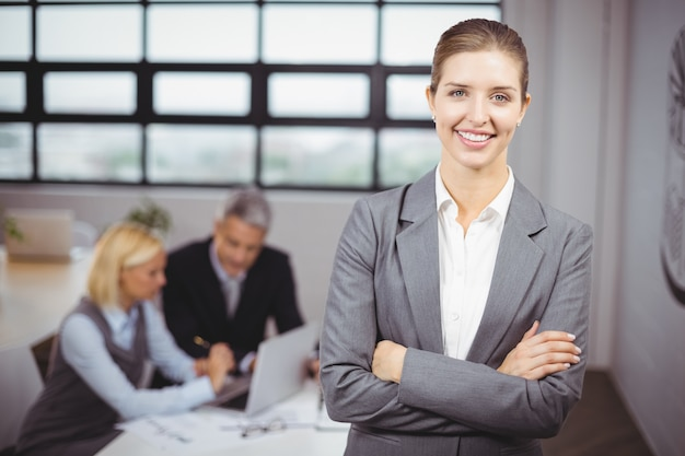 Empresaria sonriendo mientras empresarios sentados en segundo plano.