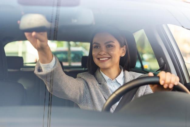 Empresaria sonriente ajustando el espejo retrovisor de su coche
