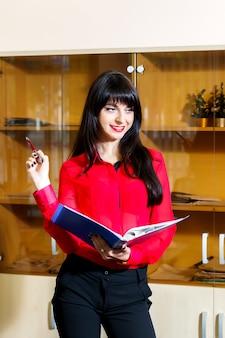 Empresaria sonriente en una blusa roja con una carpeta de documentos en oficina