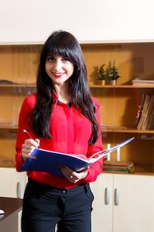 Empresaria sonriente en una blusa roja con una carpeta de documentos en la oficina