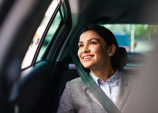 Empresaria sonriente en el coche con cinturón de seguridad