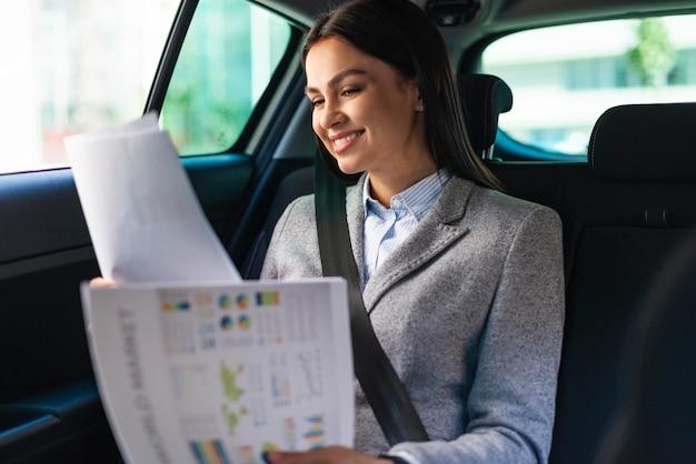 Empresaria sonriente en el coche revisando documentos