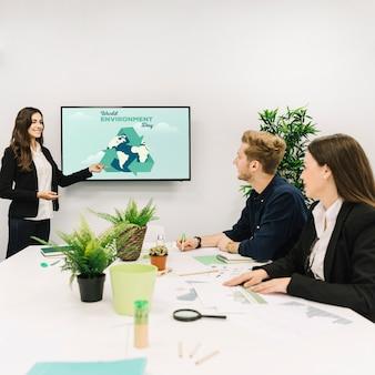 Empresaria sonriente dando presentación en el día mundial del medio ambiente a sus colegas