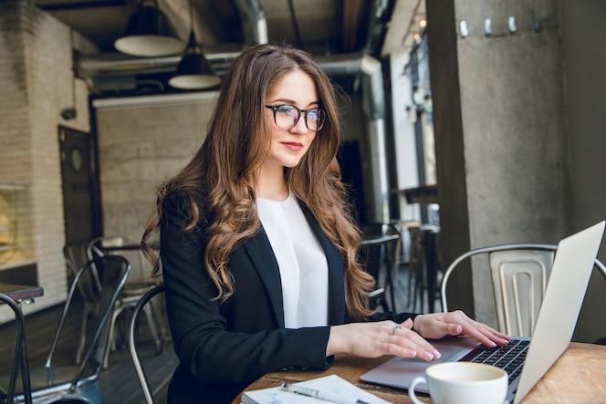 Empresaria sonriente escribiendo en un portátil sentado en un café