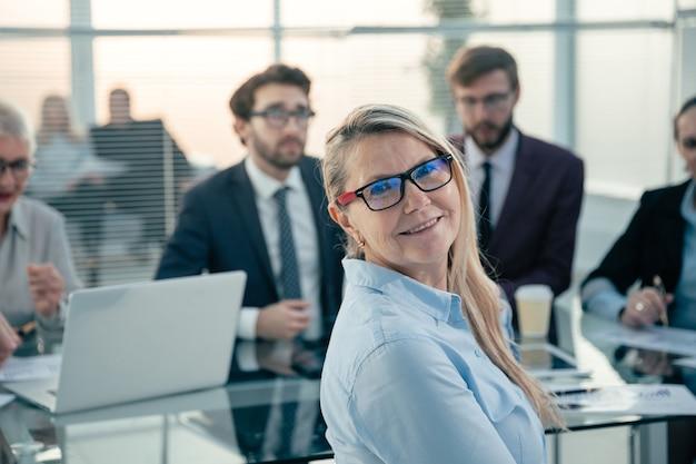 Empresaria sonriente iniciando una reunión de trabajo con el equipo empresarial