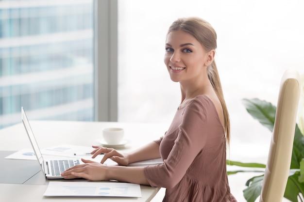 Empresaria sonriente joven que se sienta en el escritorio de oficina que mira la cámara