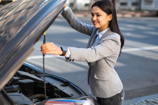 Empresaria sonriente levantando el capó del coche