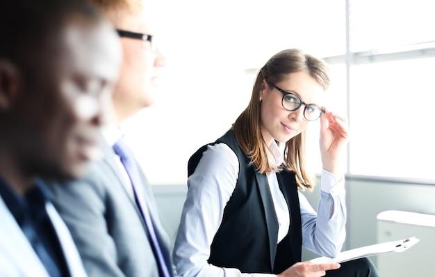 Empresaria sonriente mirando a la cámara en el seminario con sus colegas cerca
