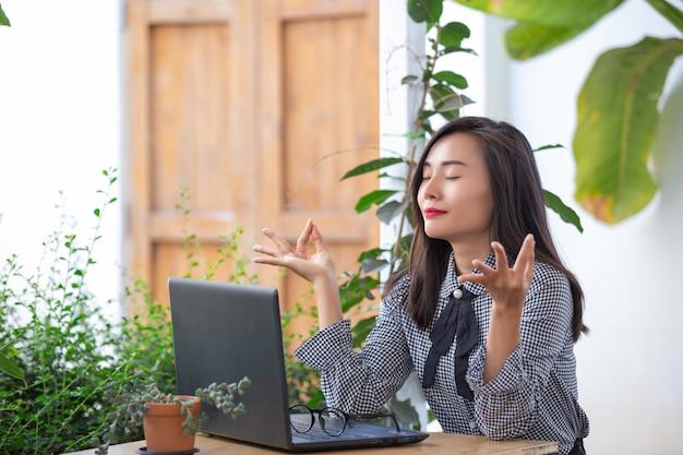 La empresaria sonriente muestra gestos para meditar