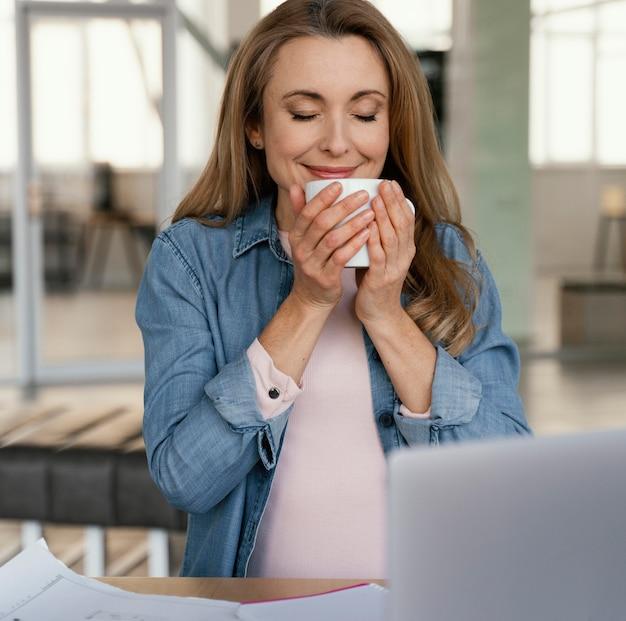 Empresaria sonriente oliendo su café de la mañana