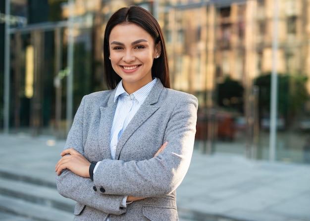 Empresaria sonriente posando al aire libre con los brazos cruzados y copie el espacio