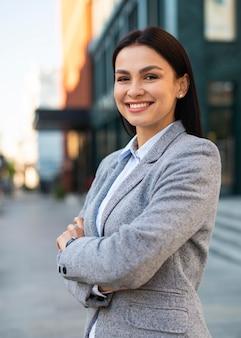 Empresaria sonriente posando en la ciudad con los brazos cruzados