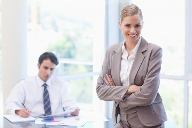 Empresaria sonriente posando mientras su colega está trabajando