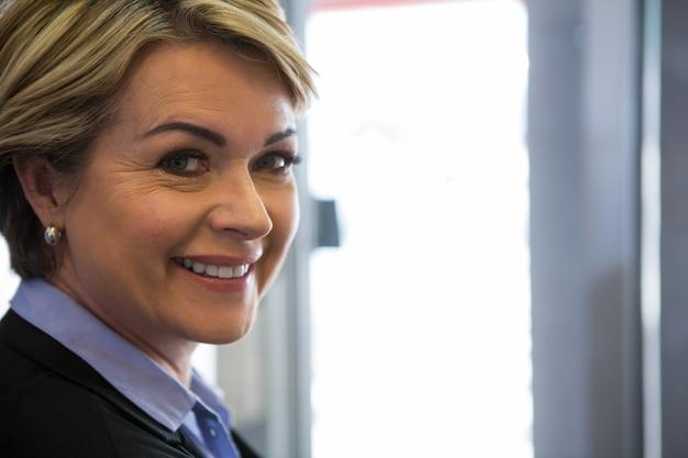 Empresaria sonriente que se coloca en el aeropuerto