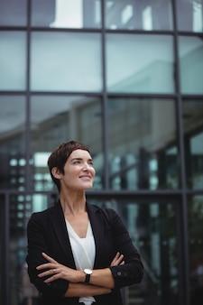 Empresaria sonriente que se coloca en premisas de oficina