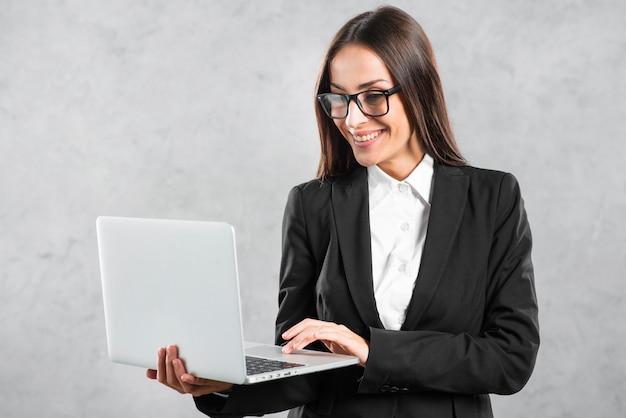 Empresaria sonriente que mira la computadora portátil en su mano contra el muro de cemento