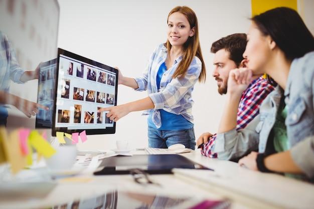 Empresaria sonriente que muestra la pantalla de la computadora a los compañeros de trabajo