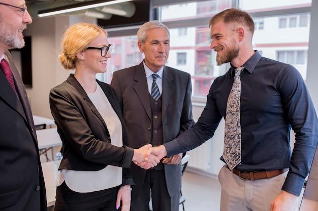 Empresaria sonriente que sacude la mano con el hombre de negocios en la oficina
