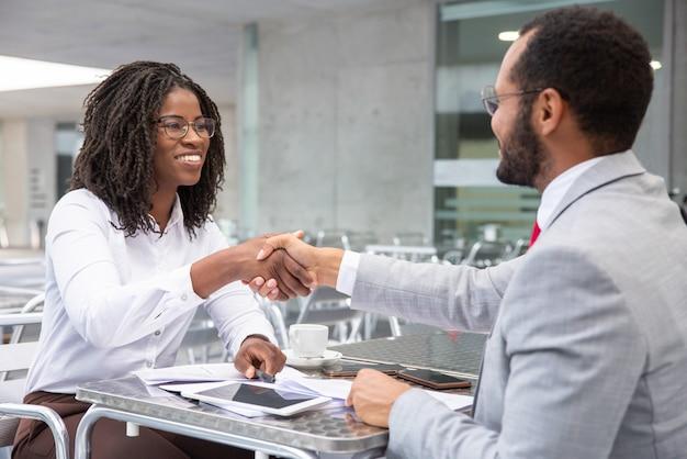 Empresaria sonriente que sacude las manos con el socio